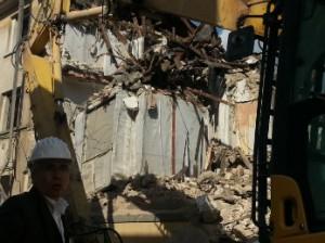 Un momento del crash test pubblico eseguito all'Aquila nel maggio 2014: un palazzo in piazza Santa Maria di Farfa è stato demolito simulando un sisma di alttissima intensità. In primo piano Antonio D'Intino inventore della Stanza Antisismica e dietro la Stanza che si scorge integra tra le macerie
