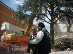 Un giornalista intervista Antonio D'Intino, inventore della Stanza Antisismica, durante il crash test dell'Aquila: a destra i primi crolli dell'edificio