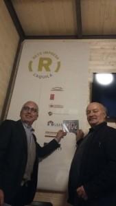Antonio D'Intino e mario Ciammitti (a dx) davanti alle insegne di Rete Impresa sullo sfondo della gabbia d'acciaio lasciata a vista